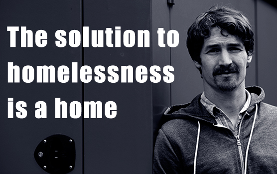 """Man standing next to text that says, """"The solutions to homelessness is a home"""""""